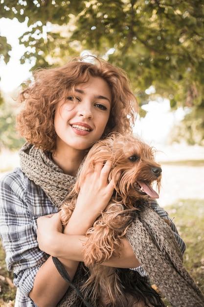 Mulher encantadora, acariciando o cão no parque Foto gratuita