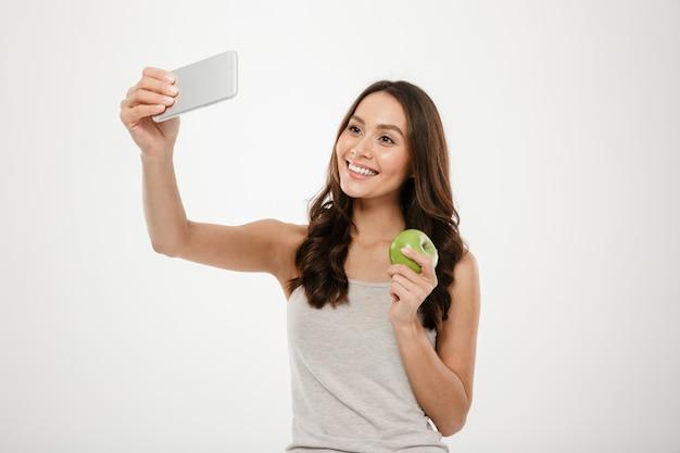 Mulher encantadora atraente fazendo selfie no celular prata e segurando suculenta maçã verde, isolada sobre parede branca Foto gratuita