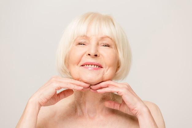 Mulher encantadora, bonita e velha tocando a pele macia e perfeita do rosto com os dedos, sorrindo para a câmera sobre fundo cinza, usando creme facial diurno e noturno, procedimentos de cosmetologia Foto Premium