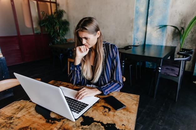 Mulher encantadora de casaco azul, olhando para a tela do computador. foto interna da estudante de cabelos compridos, estudando no café. Foto gratuita