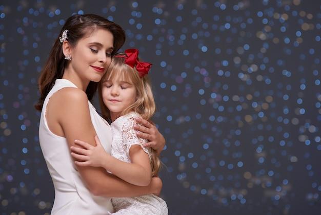 Mulher encantadora e filha apaixonada se abraçam Foto gratuita