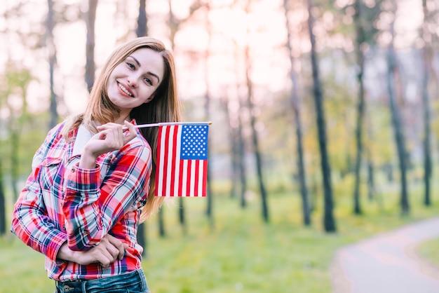 Mulher encantadora engraçada posando com a bandeira americana Foto gratuita
