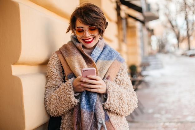 Mulher encantadora usando smartphone na rua Foto gratuita