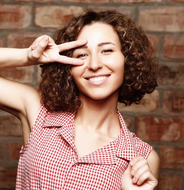 Mulher encaracolada atraente na parede de tijolo Foto Premium