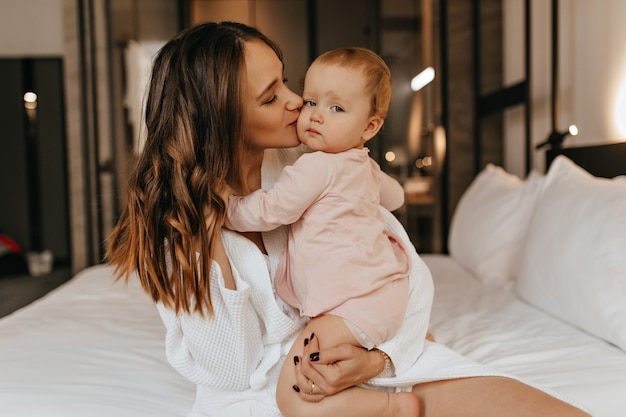 Mulher encaracolada de cabelos escuros beija amorosamente sua filha. foto de uma jovem mãe de jaleco branco e o filho no quarto. Foto gratuita