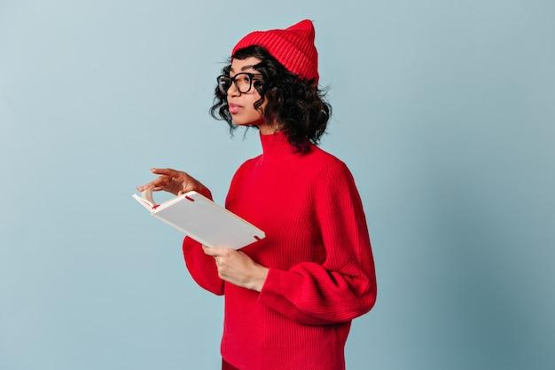 Mulher encaracolada de óculos segurando um caderno Foto gratuita