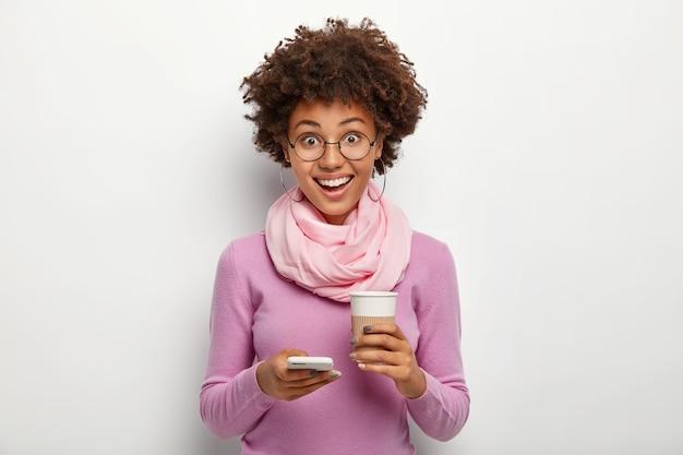 Mulher encaracolada divertida e simpática usa celular e bebe café para viagem, está de bom humor, surfa nas redes sociais Foto gratuita