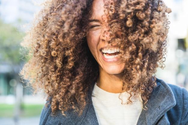 Mulher encaracolada rindo e balançando a cabeça Foto Premium