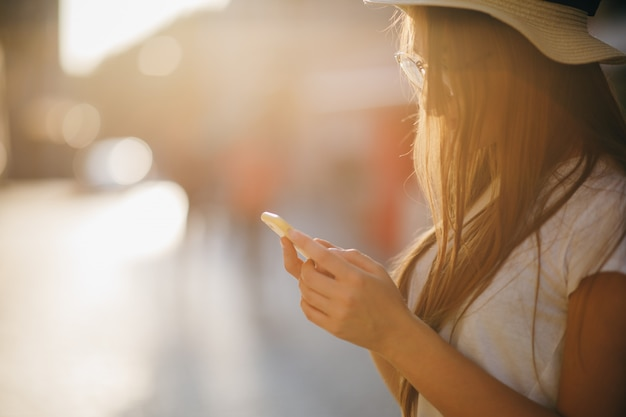 Mulher encaracolado viajante de chapéu e óculos com um telefone nas mãos, em uma primavera brilhante ao sol Foto Premium