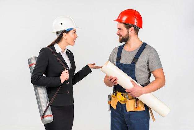 Mulher engenheiro e construtor com whatman falando Foto gratuita