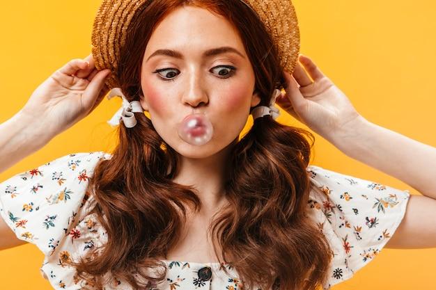 Mulher engraçada coloca no barco e olha para a bolha de goma de mascar. retrato de jovem com dois rabos de cavalo. Foto gratuita