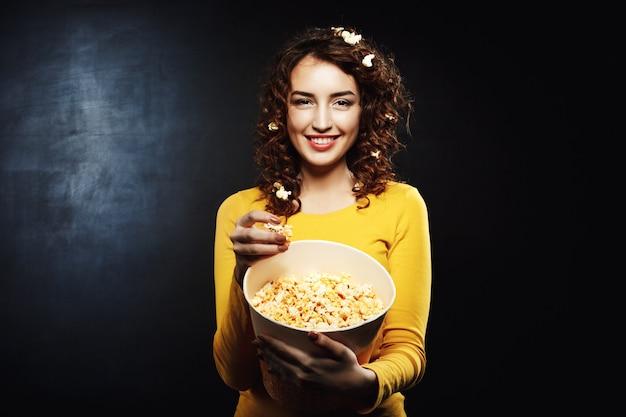 Mulher engraçada com pipoca no cabelo, sorrindo e olhando em linha reta Foto gratuita