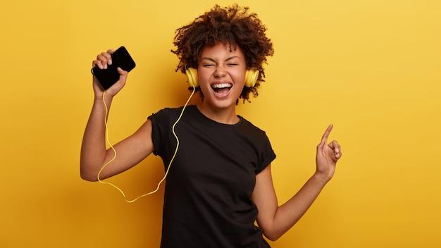 Mulher engraçada de pele escura se sente bem, dança no ritmo, agita as mãos levantadas, canta junto com a música, usa fones de ouvido Foto gratuita