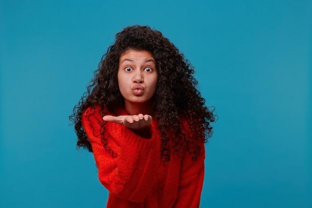 Mulher engraçada em suéter vermelho com adorável cabelo preto encaracolado olhando para a frente e mandando um beijo no ar Foto gratuita