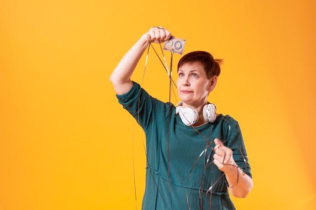Mulher engraçada sênior, olhando para uma fita cassete Foto gratuita
