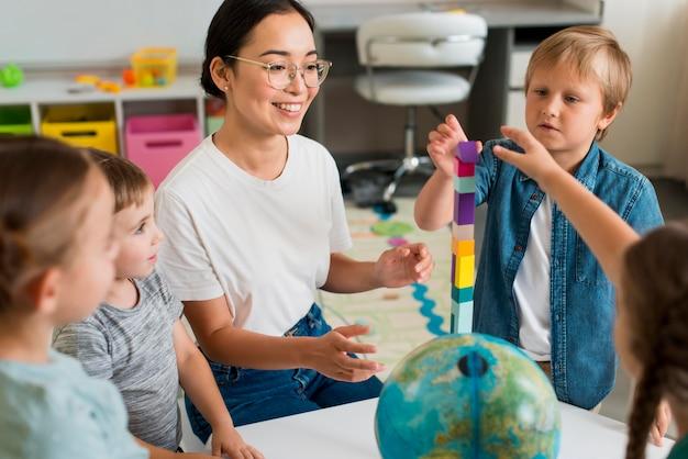 Mulher ensinando alunos a brincar com a torre colorida Foto Premium