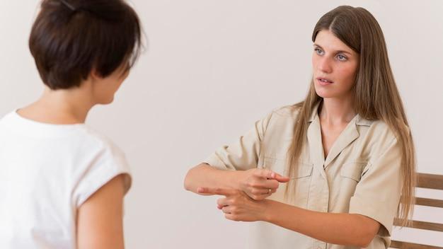 Mulher ensinando linguagem de sinais para outra pessoa Foto Premium