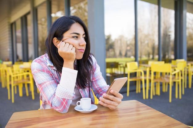 Mulher entediada sentado na rua café com smartphone e café Foto gratuita