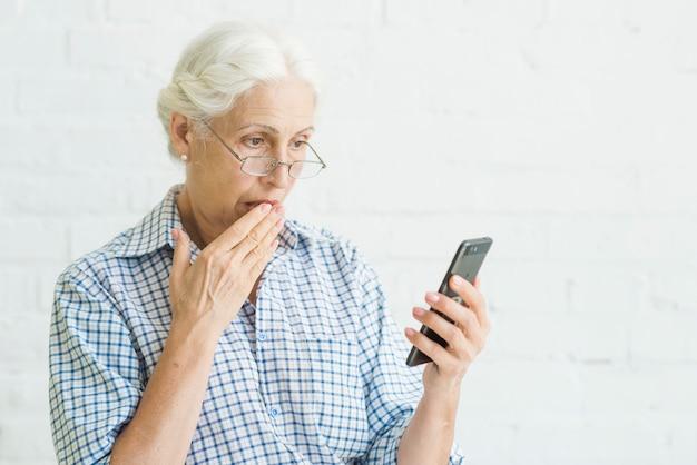 Mulher envelhecida chocada olhando para celular contra o pano de fundo Foto gratuita