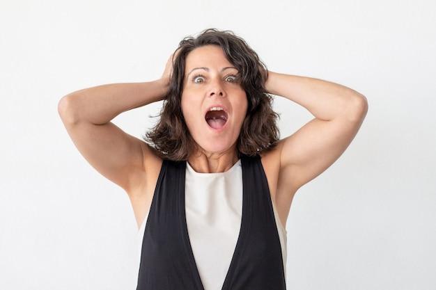 Mulher envelhecida média chocada que grita Foto gratuita