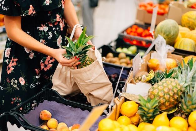Mulher escolhe mercado de alimentos de frutas e legumes Foto Premium