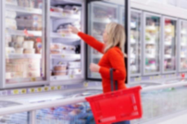 Mulher escolhe produtos no departamento de congelamento em um supermercado. alimentação saudável e estilo de vida. vista lateral. borrado. Foto Premium
