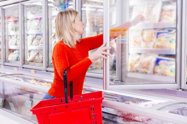 Mulher escolhe produtos no departamento de congelamento em um supermercado. alimentação saudável e estilo de vida. vista lateral. Foto Premium