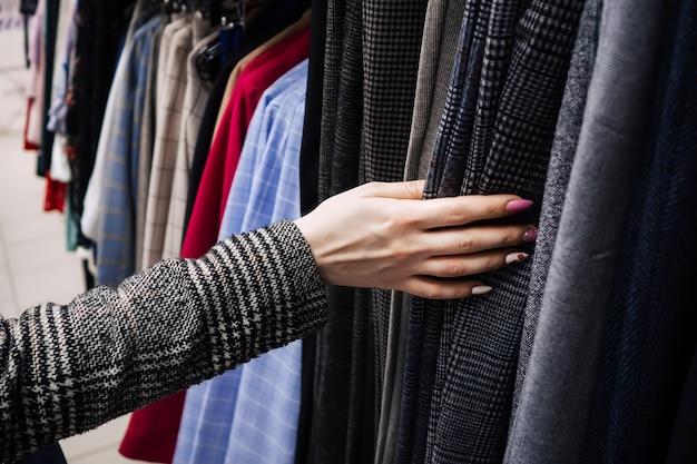 Mulher escolhe roupas com a mão na loja Foto Premium