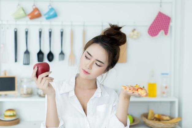Mulher escolhendo entre apple e pizza Foto gratuita