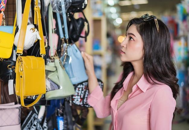 Mulher, escolher, e, shopping, bolsa, em, loja Foto Premium