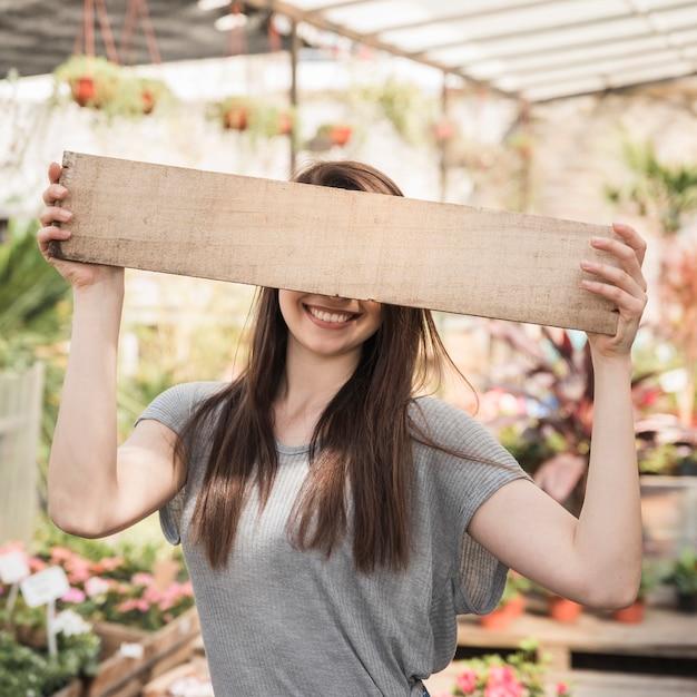 Mulher, escondendo, dela, olhos, atrás de, prancha madeira Foto gratuita