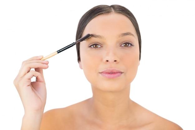 Mulher escovando sua sobrancelha Foto Premium