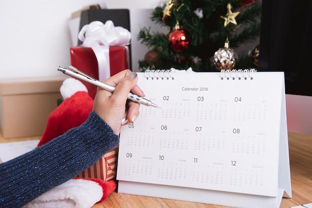 Mulher escrevendo planejador de calendário no feriado de natal no escritório com decoração de natal Foto Premium