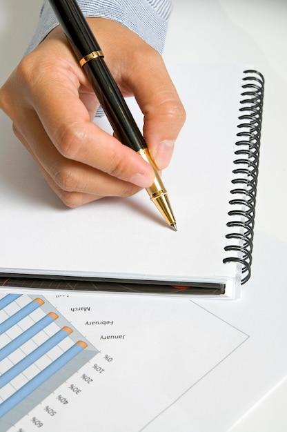 Mulher escrever na agenda em branco com caneta preta Foto Premium