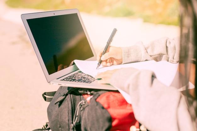Mulher, escrita, mão, caderno, ensolarado, dia Foto gratuita