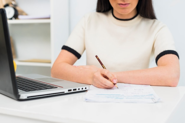 Mulher, escrita, papeis, tabela, laptop Foto gratuita
