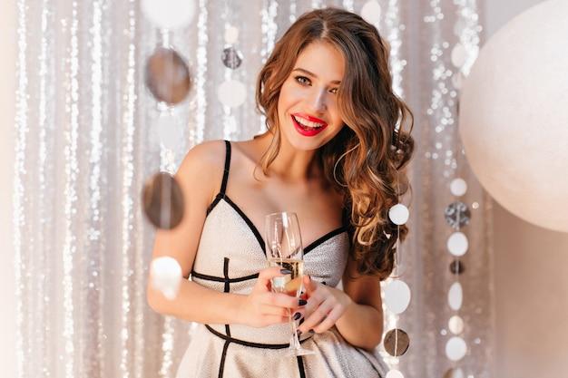 Mulher eslava com cabelo comprido encaracolado e lábios vermelhos fica na luz brilhante, se alegra no ano novo e bebe champanhe saboroso. retrato de senhora comemorando 2019 em festa em sala brilhante Foto gratuita