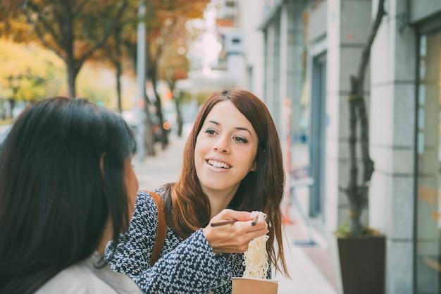 Mulher espanhola ouvindo a amiga na rua enquanto toma comida asiática Foto Premium