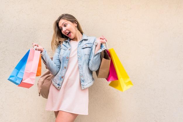 Mulher espantada, em pé com sacos de compras na parede Foto gratuita