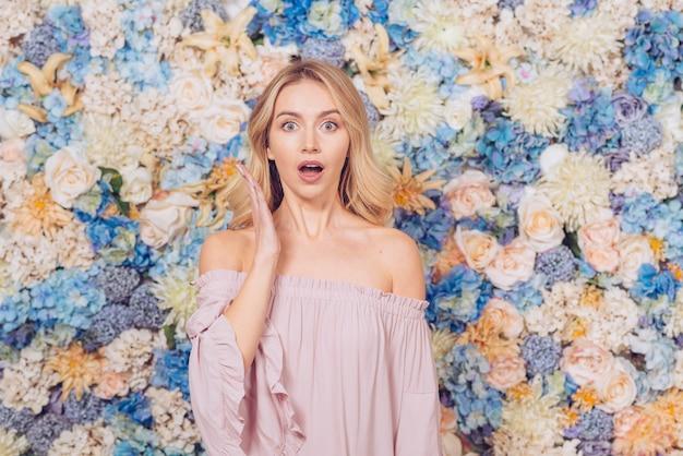 Mulher espantada em pé no fundo de flores Foto gratuita