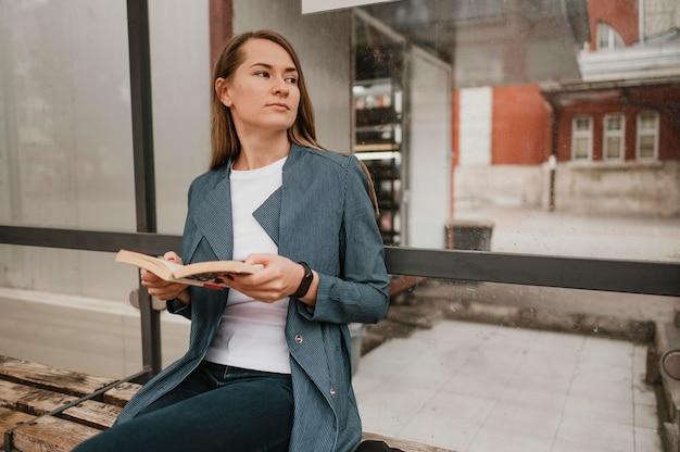 Mulher esperando o ônibus e lendo Foto gratuita