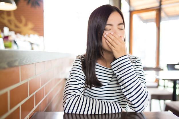 Mulher espirrando em um café Foto Premium
