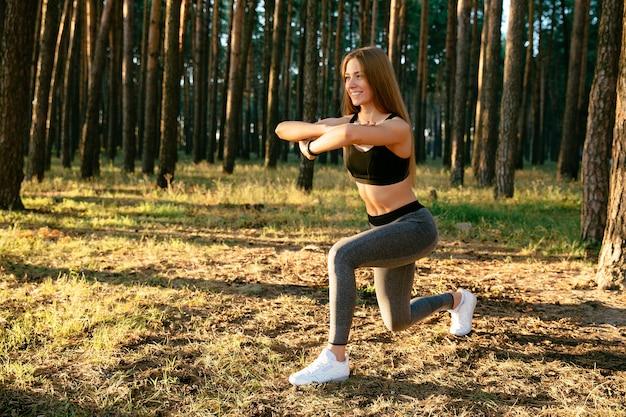 Mulher esportiva alegre na parte superior do tanque e leggings, fazendo alongamento para o corpo Foto gratuita