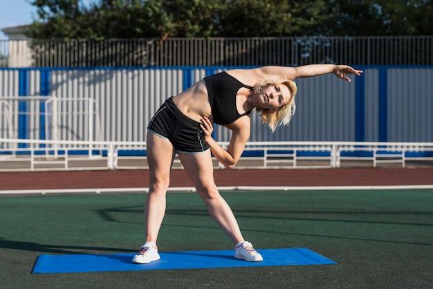 Mulher esportiva aquecimento antes do treino Foto gratuita
