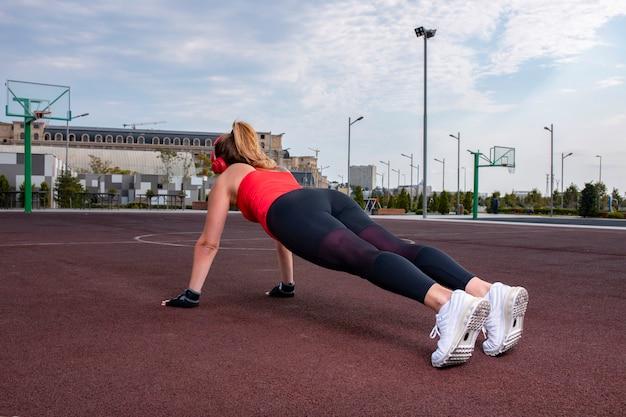Mulher esportiva em roupas de alongamento, fazendo atividade de aquecimento na terra. Foto gratuita
