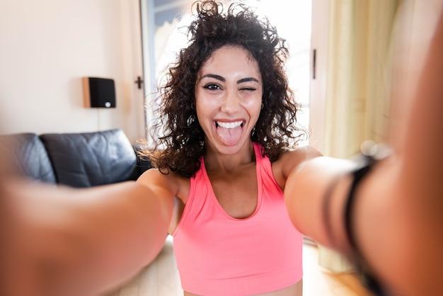 Mulher esportiva em roupas esportivas está sentada no chão com halteres, tirando uma selfie na sala de estar Foto Premium