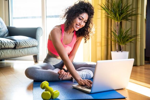 Mulher esportiva em roupas esportivas está sentada no chão com halteres usando um laptop na sala de estar Foto Premium