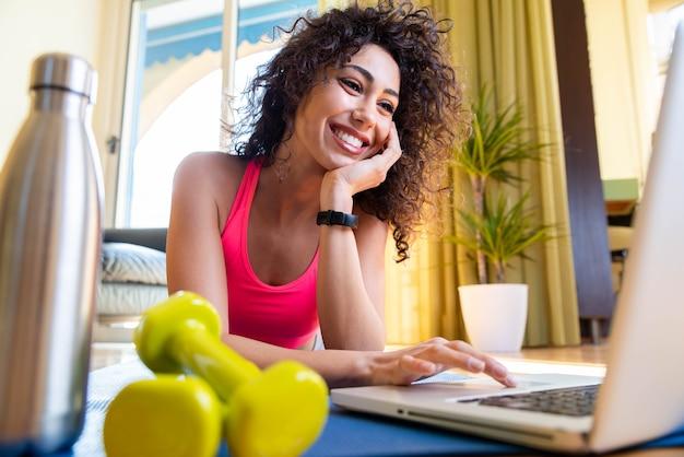 Mulher esportiva em roupas esportivas está sentada no chão com halteres usando um laptop pc na sala de estar Foto Premium