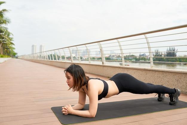 Mulher esportiva fazendo exercício de prancha ao ar livre Foto gratuita