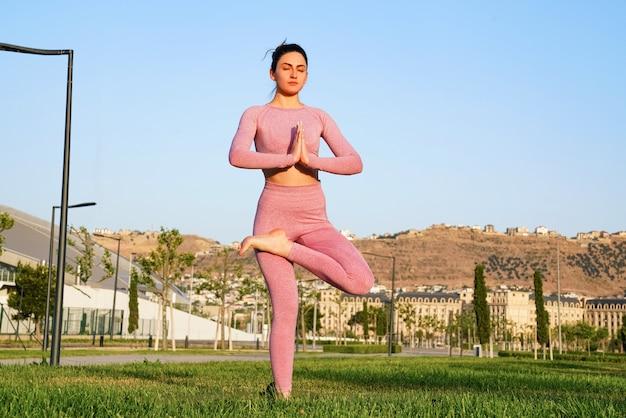 Mulher esportiva feliz praticando ioga ao ar livre Foto gratuita